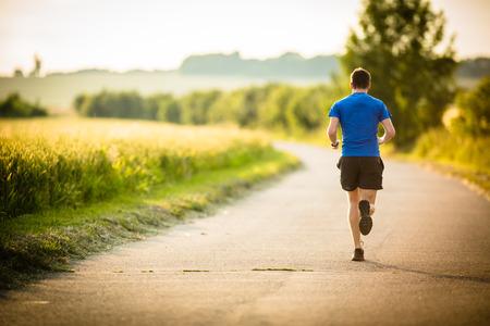 фитнес: Мужской спортсмен  бегун на дороге - толчковой тренировки благополучия концепции