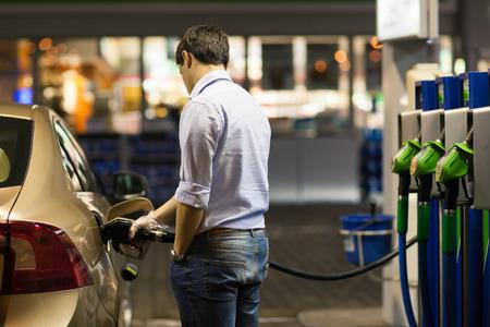 주유소에서 그의 차를 연료를 공급하는 젊은 남자 스톡 콘텐츠