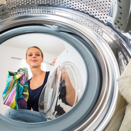 doing laundry: Housework: young woman doing laundry