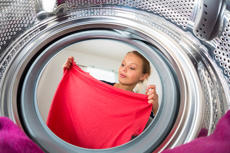 domestic task: Housework: young woman doing laundry
