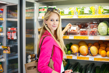produce sections: Beautiful young woman shopping for fruits and vegetables in produce department of a grocery storesupermarket