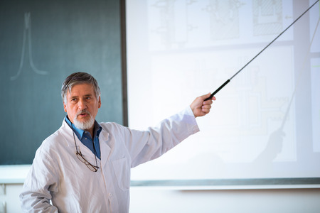 Senior chemistry professor giving a lecture in front of classroom full of students  photo