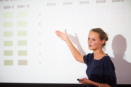 speach: Pretty, young business woman giving a presentation in a conferencemeeting setting