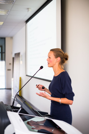 Pretty, young business woman giving a presentation in a conferencemeeting setting  photo