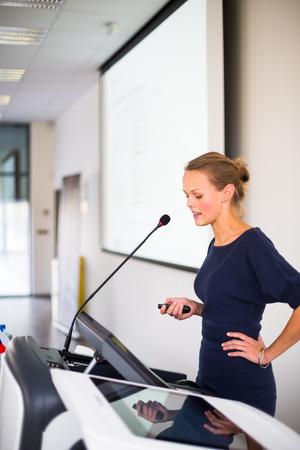 Pretty, joven mujer de negocios dando una presentación en un entorno de conferencia / reunión (DOF, imagen en color entonado) Foto de archivo - 25800508