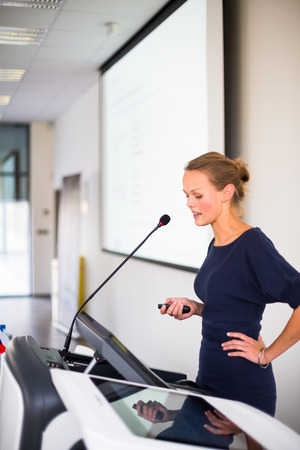auditorium: Pretty, young business woman giving a presentation in a conferencemeeting setting (shallow DOF; color toned image) Stock Photo