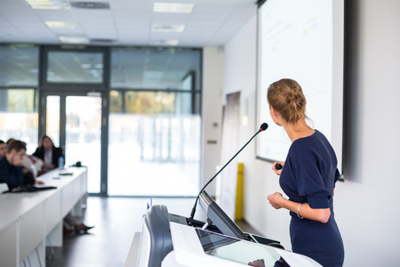 Pretty, young business woman giving a presentation in a conference/meeting setting  photo