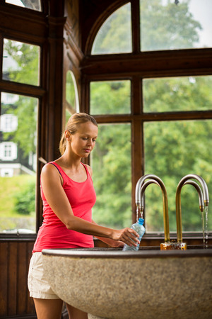 carlsbad: Young woman filling a plastic bottle with healthy mineral water from a wellspring in a spa