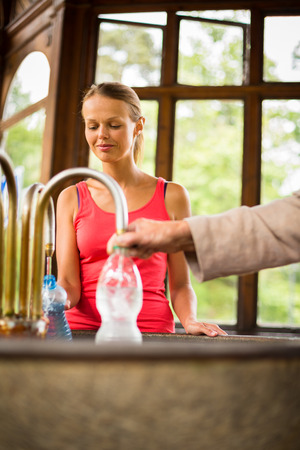 carlsbad: Young woman filling a plastic bottle with healthy mineral water from a wellspring in a spa  Stock Photo