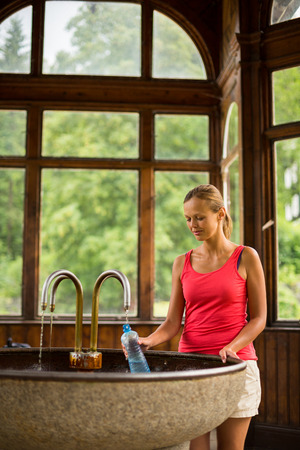 therapy geothermal: Young woman filling a plastic bottle with healthy mineral water from a wellspring in a spa  Stock Photo