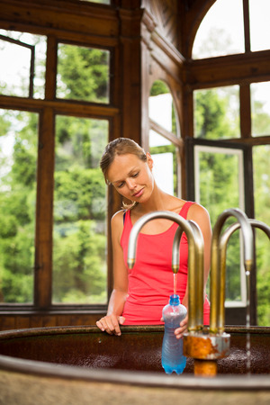 Magnesium: Young woman filling a plastic bottle with healthy mineral water from a wellspring in a spa  Stock Photo