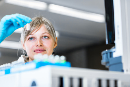 Portrait of a female researcher carrying out research in a chemistry lab (color toned image; shallow DOF) Imagens