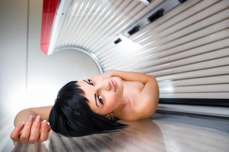 solarium: Pretty young woman tanning her skin in a modern solarium