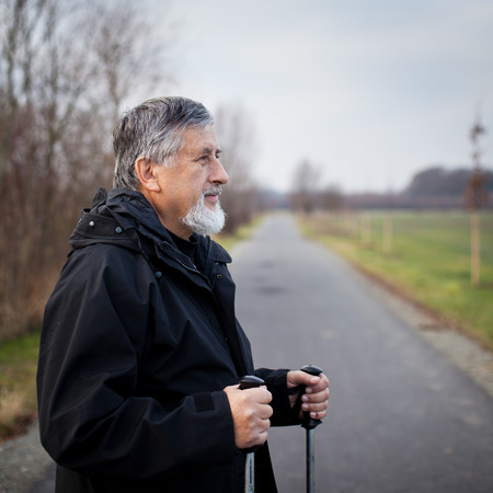 Senior man nordic walking, enjoying the outdoors, the fresh air, getting the necessary exercise Stock Photo