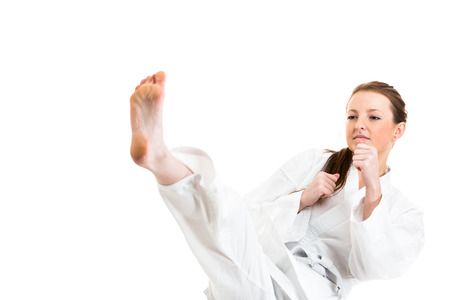 Mooie Kaukasisch, jonge, vrouw maakt een schop in karate kimono op een witte achtergrond
