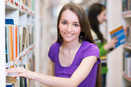 mba: In the library - pretty, female student searching for books in a high schooluniversity library (color toned image)
