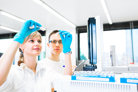 Two young researchers carrying out experiments in a lab photo
