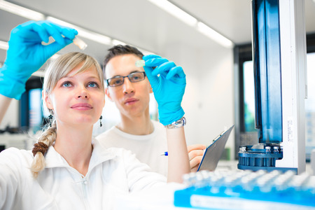 science class: Two young researchers carrying out experiments in a lab