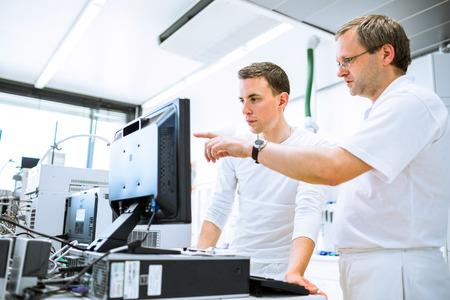 bata de laboratorio: El equipo de investigadores que llevan a cabo experimentos en un laboratorio Foto de archivo