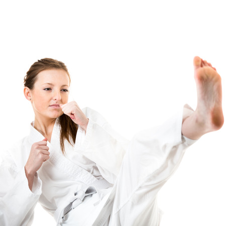 Beautiful caucasian, young, woman makes a kick in karate kimono on white background photo