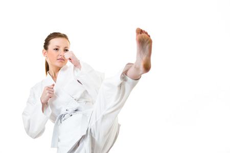 karate kick: Beautiful caucasian, young, woman makes a kick in karate kimono on white background
