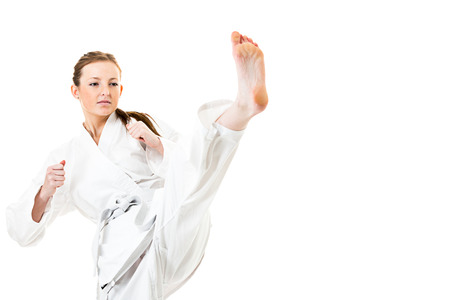Beautiful caucasian, young, woman makes a kick in kimono on white background photo