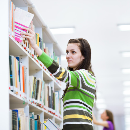 pretty female student searching for books in a high school/university library photo