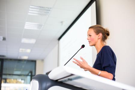 Mooie, jonge zakenvrouw het geven van een presentatie in een conferentie  vergadering instelling (ondiepe DOF, kleuren getinte afbeelding)