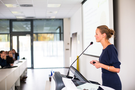 speaker: Pretty, young business woman giving a presentation in a conferencemeeting setting (shallow DOF; color toned image) Stock Photo