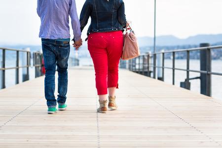 atraer: Los opuestos se atraen - joven pareja bastante desproporcionada caminando sobre un muelle Foto de archivo