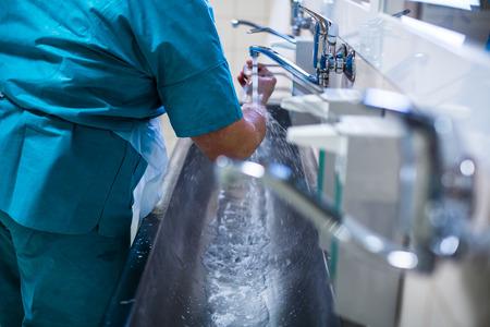 Chirurg in het ziekenhuis wassen thorouughly zijn handen voor het uitvoeren van een operatie (kleur getinte afbeelding, ondiepe DOF)