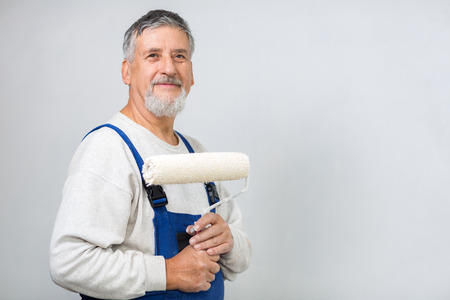Senior man painting a wall in his home photo