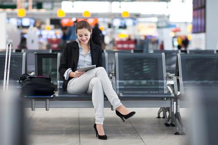 彼女の飛行を待っている間彼女のタブレット コンピューターを使用して、空港での若い女性の乗客