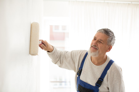 Senior man painting a wall in his home, smiling, enjoying the work photo