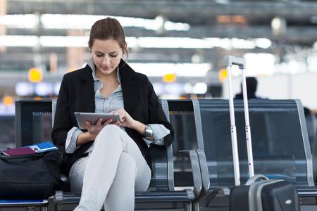 Junge weibliche Fluggast am Flughafen, mit ihrem Tablet-Computer während des Wartens auf ihren Flug