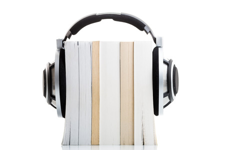 Audiobook concept - listen to your books in HD quality; hi-end hifi headphones over multiple books on white photo