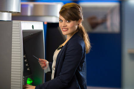 indebt: Pretty, young woman withdrawing money from her credit card in at an ATM (shallow DOF; color toned image) Stock Photo