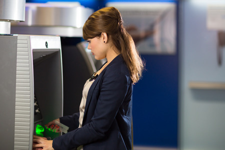 Pretty, young woman withdrawing money from her credit card in at an ATM