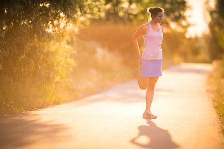 Young woman running outdoors on a lovely sunny summer evening  shallow DOF; color toned image  photo