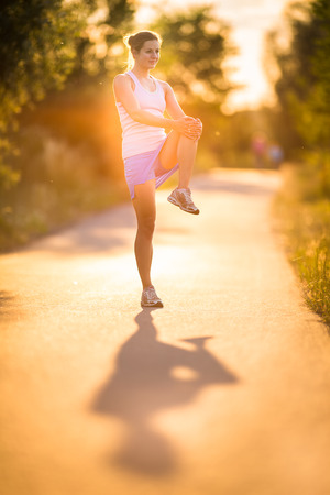 Young woman running outdoors on a lovely sunny summer evening  shallow DOF; color toned image  Stock Photo