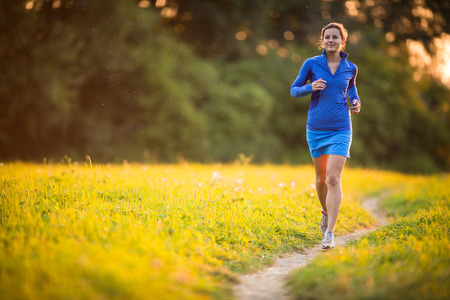 skinny woman: Young woman running outdoors on a lovely sunny summer evening  shallow DOF; color toned image  Stock Photo