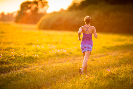 Young woman running outdoors on a lovely sunny summer evening (shallow DOF; color toned image) photo