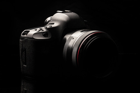 dslr camera: Professional modern DSLR camera low key image - Modern DSLR camera with a very wide aperture lens on