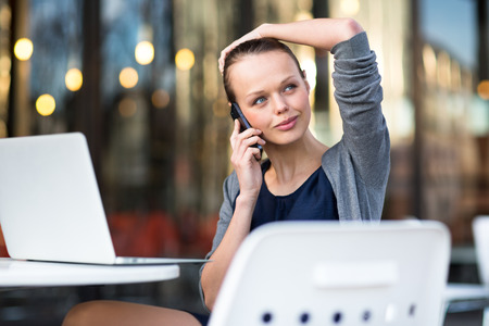 important phone call: Portrait of a sleek young woman calling on a smartphone and using her laptop in a an urbancity context (shallow DOF; color toned image)