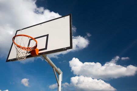 score under: Basketball hoop against  lovely blue summer sky with some fluffy white clouds