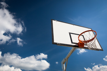 street shots: Basketball hoop against  lovely blue summer sky with some fluffy white clouds