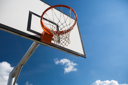 high school basketball: Basketball hoop against  lovely blue summer sky with some fluffy white clouds