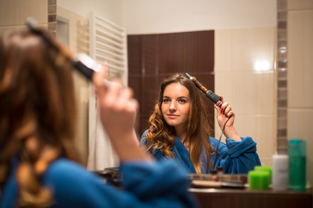 hair curler: Pretty, young woman curling her hair in front of her bathroom mirror