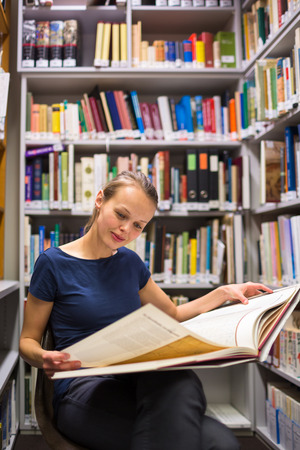 Pretty, young woman studying an old book in archives photo