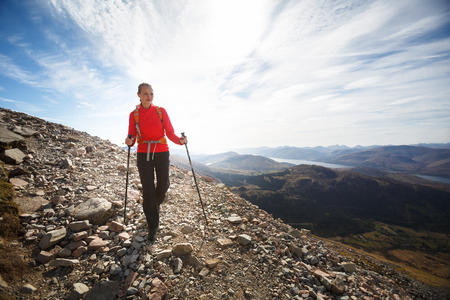 woman hiking: Pretty, young female hiker going uphill